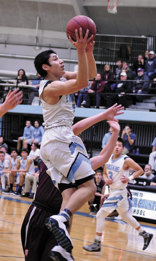 T-R PHOTO BY THORN COMPTON • South Tama County senior Gabe Shields, center, floats in the lane while going up for a shot at the buzzer at the end of the first quarter in the Trojans' 65-48 win over Grundy Center on Thursday in Tama.