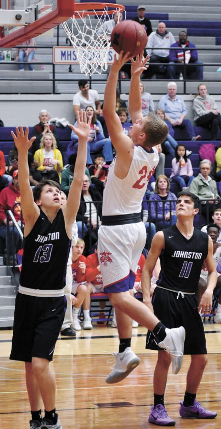 T-R PHOTO BY THORN COMPTON • Marshalltown junior Jacob Smith, center, takes to the sky to lay the ball in over Johnston's Bo Sandquist (13) during the second half of the Bobcats' loss to the Dragons at home on Friday.