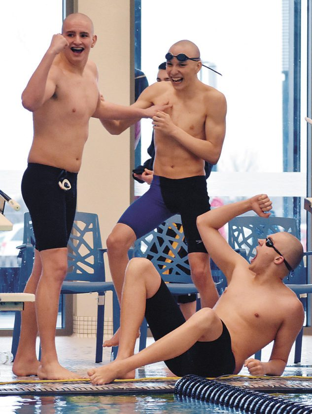 T-R PHOTO BY THORN COMPTON • Marshalltown swimmers Carson Beals, left, Nash Perisho, center, and Gage Petty celebrate as Ryne Downey finishes up the final leg of the 400-yard freestyle relay on Saturday at the Bobcats' district meet. The boys are celebrating a seven-second time cut for the race, a time that qualified the 400 free relay for a state championship berth.