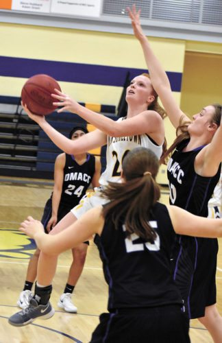 T-R PHOTO BY THORN COMPTON • Marshalltown Community College sophomore Alyssa Roth, center, glides through the lane while attempting a shot as DMACC's Molly Mitchell, right, and Grace Stalzer (25) defend during the Tigers' loss to the Bears on Wednesday.