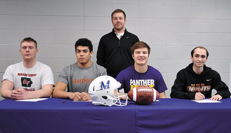 T-R PHOTO BY THORN COMPTON • Four Marshalltown High School seniors gathered in the team room in the Roundhouse to sign their letters of intent on Wednesday. Pictured are, from left, Mason Monk, Spencer Finch, Chayton French and Ryan Huffman, and Bobcat head football coach Adam Goodvin, standing.