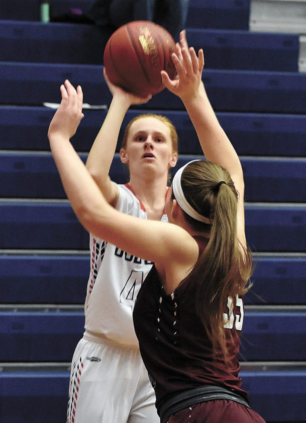 T-R PHOTO BY THORN COMPTON • Marshalltown senior Kassy Vest, behind, shoots over Dowling Catholic's Jacey Koethe during the first quarter of the Bobcats' loss to the Maroons in their final regular season game on Thursday night.