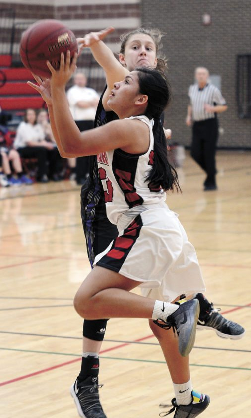 T-R PHOTO BY ROSS THEDE • Meskwaki freshman point guard Deandra Navarro, drives in for a layup past GMG junior Mable Dieleman during the second half of Thursday's Class 1A regional girls' basketball game at Meskwaki Settlement.