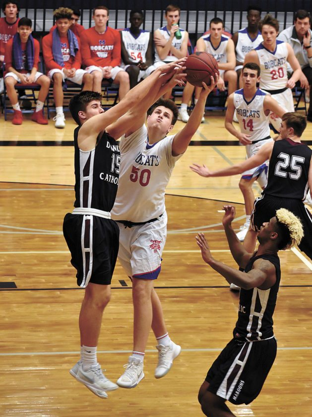 T-R PHOTO BY THORN COMPTON • Marshalltown senior Luke Appel (50) fights for a rebound Dowling Catholic's Luke Yacinich during the Tigers' home loss to the Maroons on Thursday.