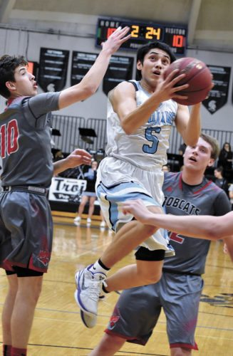 T-R PHOTO BY THORN COMPTON • South Tama County senior Gabe Shields (5) flies through the lane while putting up a layup over three West Dubuque defenders during the first quarter of the Trojans home loss to the Bobcats on Friday. Shields led STC with 18 points in the regular-season home finale.