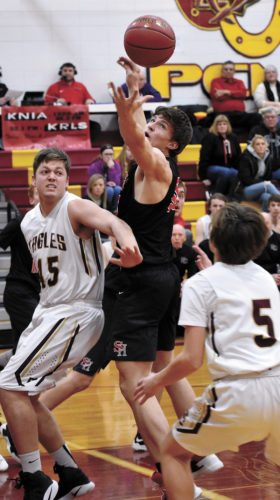 T-R PHOTO BY THORN COMPTON • South Hardin senior Kevin Rewoldt, center, looks to haul in a rebound while Pella Christian defenders Alex Huisman (45) and Dan Jungling (5) work on boxing Rewoldt out during the Eagles' district-opening win over the Tigers in Monroe on Monday night.