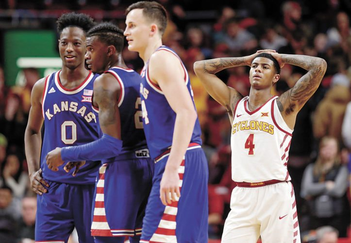 AP PHOTO • Kansas' Marcus Garrett (0), Lagerald Vick and Mitch Lightfoot chat as Iowa State's Donovan Jackson (4) stands nearby during the second half of a Big 12 Conference basketball game Tuesday at Hilton Coliseum in Ames. Kansas won 83-77.