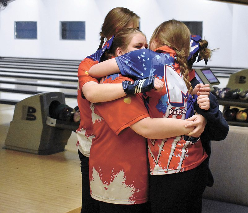T-R PHOTO BY THORN COMPTON • Marshalltown senior Karlie Potter, center, is hugged by teammates Haley Bell, right, and Kylee Witt as she's overcome with emotion after winning the individual district title at Wayward Social on Tuesday. Potter enters the state tournament as the top individual qualifier with a series score of 477.