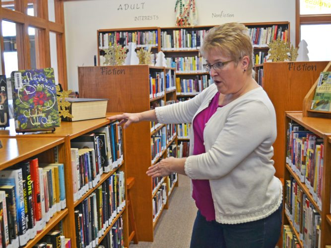 T-R PHOTO BY SARA JORDAN-HEINTZ The Albion Municipal Library and Heritage Center has embarked on a fundraising campaign to cover the costs of obtaining custom-made oak cabinetry, that would be installed underneath select bookcases in the library. Here, Library Director Julia Ohrt shows how this addition will also make it easier for patrons to access shelves that are currently very low to the ground.