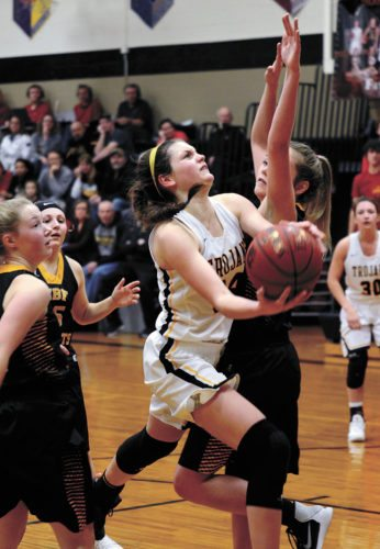 T-R PHOTO BY ROSS THEDE • West Marshall senior Isabelle Gradwell, left, glides in for a layup against Eddyville-Blakesburg-Fremont defender Kennedy Landgrebe during the second half of Wednesday's Class 3A Region 7 semifinal in State Center. Gradwell had a game-high 23 points in the Trojans' 59-34 win.