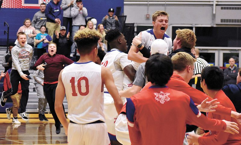 T-R PHOTO BY THORN COMPTON • The Roundhouse erupts as Marshalltown boys' basketball players — including Jacob Smith, top — are mobbed in the middle of the court after the Bobcats beat Class 4A No. 3 Des Moines North on a late layup by Luke Appel on Friday night.