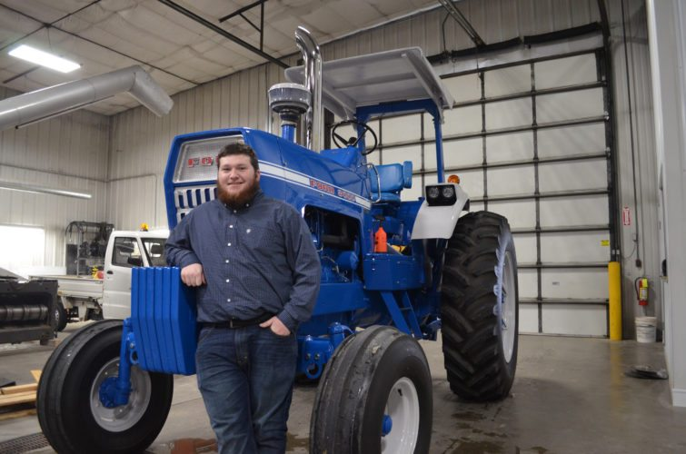 CONTRIBUTED PHOTO Nate Casady stands next to this fully-restored 1969 Ford 8000 tractor. The tractor had previously been his grandfather's for most of the tractor's 49 years.