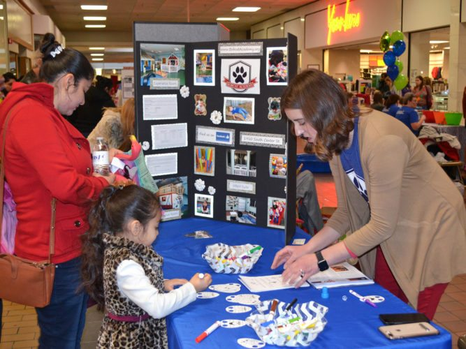 The 13th annual Healthy Family Fair, sponsored by Child Abuse Prevention Services (CAPS), was held Saturday at the Marshalltown Mall. Around 30 health-related booths were there to provide information and activities related to nutrition, development, education, dental health and general well-being of youth prenatal to age five. Pictured is Ashley Johnson, right, from Marshalltown Bobcat Academy, handing out school registration information and helping kids do arts and crafts.