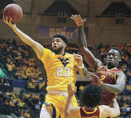 AP PHOTO • West Virginia forward Esa Ahmad (23) drives while being defended by Iowa State forward Cameron Lard (2) during the second half of a Big 12 Conference game Saturday in Morgantown, W.Va.