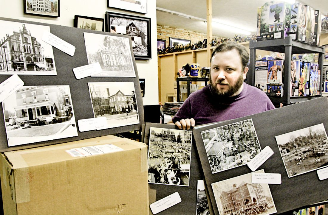 Tribune Chronicle / Robert Lebzelter Josh Nativio shows some of the prints he has collected of downtown Warren decades ago.