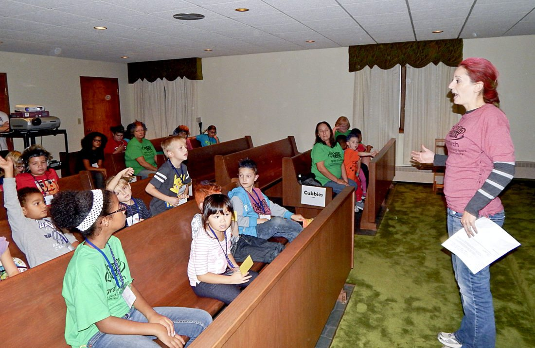 Lindsay Cameron, organizer of the AWANA Children's Ministry program at Grace United Methodist Church in Warren, speaks to children at one of the programs. The AWANA program is being offered at many area churches, and there is a different theme each week, with this event showing ''Crazy Hair Night.'' Tribune Chronicle /       Bob Coupland