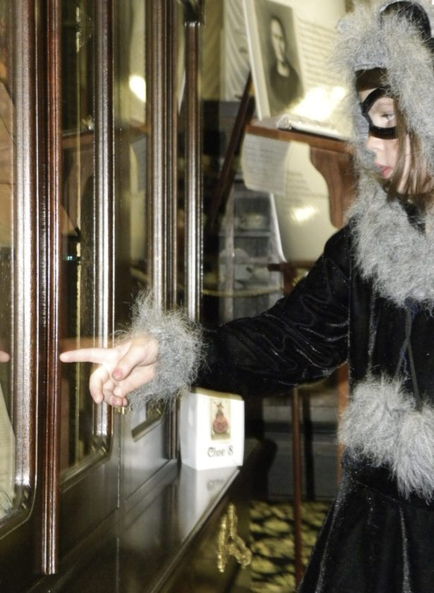 """Ciarra Kascak, 5, of Warren, points to the case containing the final """"clue"""" in the Victorian Halloween scavenger hunt Saturday at the Sutliff Museum. Kascak, dressed as a raccoon, was spending the afternoon learning through Halloween crafts and stories at the museum."""