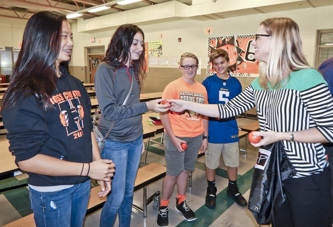 Lauren Thorp, director of recovery and youth programs at Trumbull County Mental Health and Recovery Board, presented miniature basketballs to Howland Middle School eighth-graders, from left, Kate Li, Olivia Hutchings, Ethan Miller and Thomas Depoy. The assembly included various speakers who addressed making good decisions and choices.