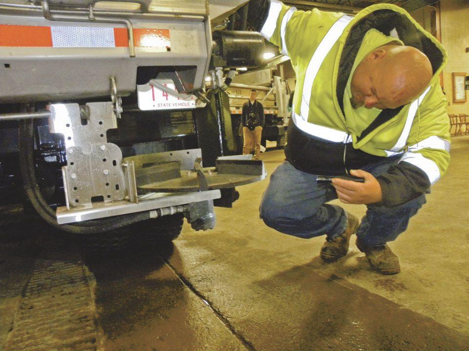 Joe Kellar, an ODOT employee, inspects a salt spreader device on the rear of one of the plow truck.