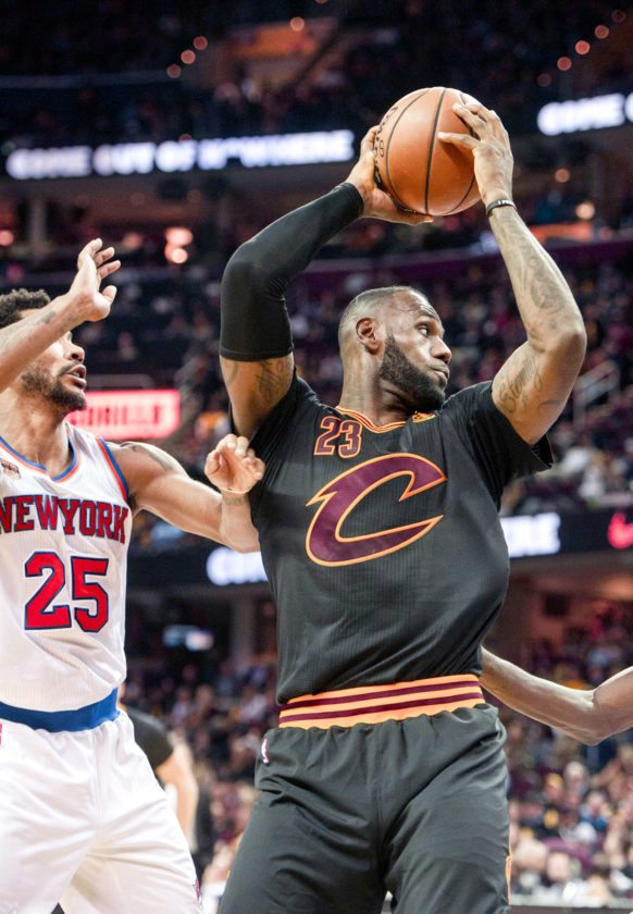 Cleveland Cavaliers' LeBron James (23) grabs a rebound in front of New York Knicks' Derrick Rose (25) during the second half of an NBA basketball game in Cleveland, Tuesday, Oct. 25, 2016. (AP Photo/Phil Long)