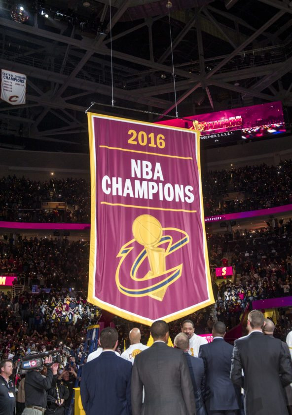Cleveland Cavaliers players and executives watch as the championship banner is raised before a basketball game against the New York Knicks in Cleveland, Tuesday, Oct. 25, 2016. (AP Photo/Phil Long)