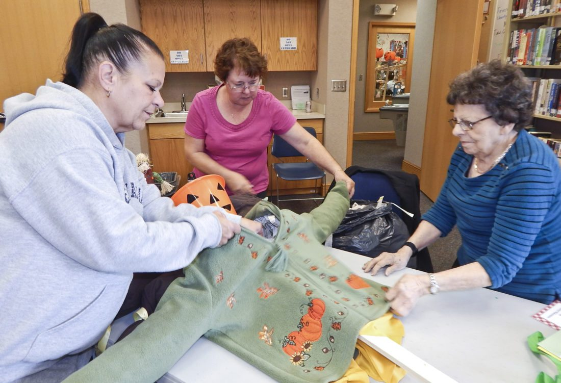 Tribune Chronicle / Bob Coupland  Friends of the Liberty Library, from left, Kim Quinlan, Becky Marx and Millie Larney, all of Liberty, work on their scarecrows at a recent program at Liberty Library Branch.