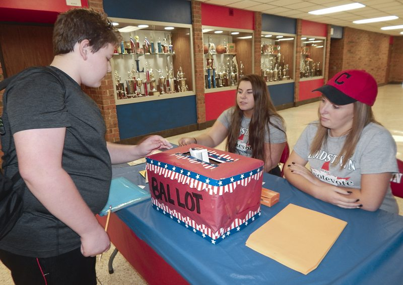 Tribune Chronicle / Bob Coupland  Nick Allen, left, an eighth-grader, places his ballot in a box during a mock election in Lordstown schools Tuesday. Helping at the event are Lindsey Burns, 16, a junior, center, and Addison Wilson, 15, a sophomore.