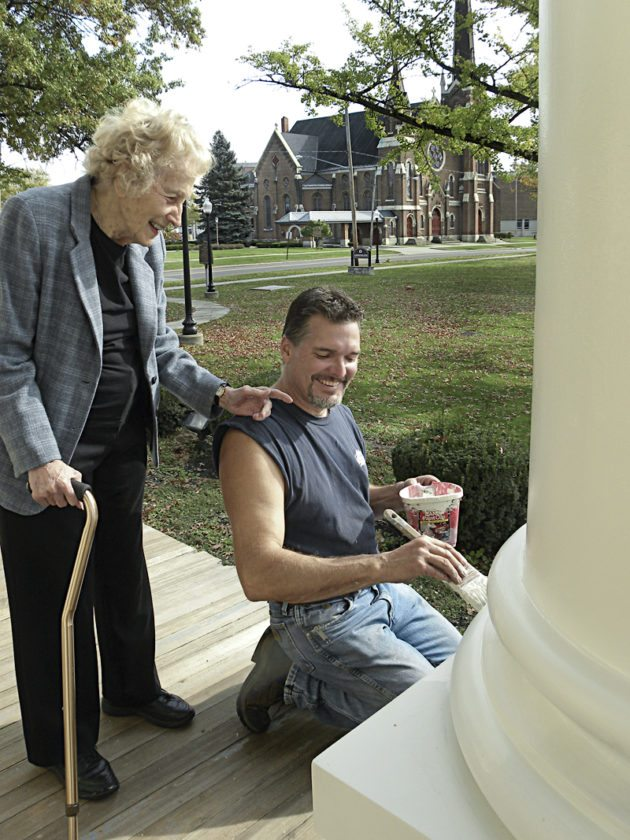 Kay Fisher, project manager of the Kinsman House Pillar restoration with Richard Thomas, woodworker and restorer.