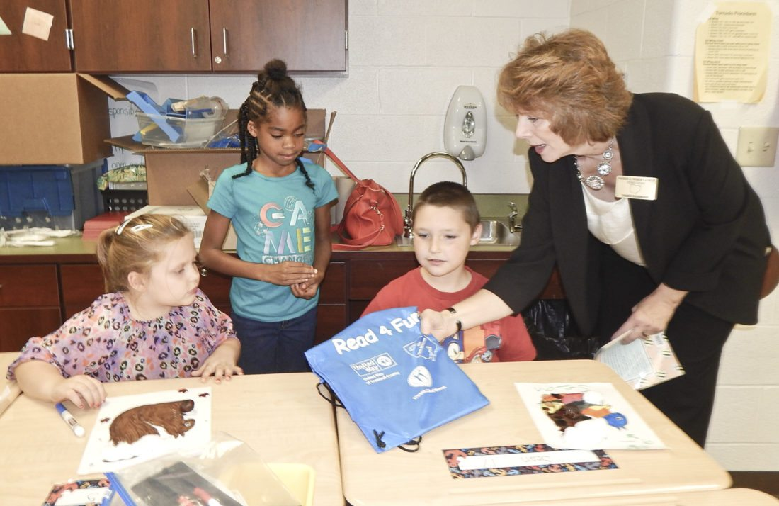 Tribune Chronicle / Bob Coupland  Sharon Drummond, right, with the Warren Junior Women's League assisted the United Way of Trumbull County recently in distributing bags filled with books, crafts and other items to second-grade students at McGuffey PK-8 School in Warren. Getting their bags are, from left, Caitlyn Hays, 7; Jalaiya Johnson, 7; and Sean Williams, 8.