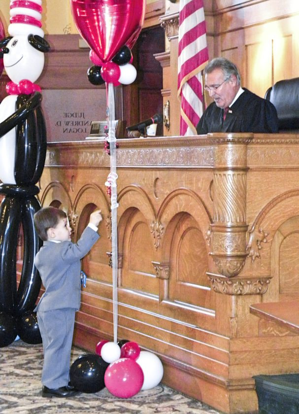 Adoptee Jerry Anderson, 2, is more interested in the balloons in front of the bench where Probate Judge James Fredericka is reading his adoption papers during a National Adoption Month program held in Trumbull County Court on Friday.
