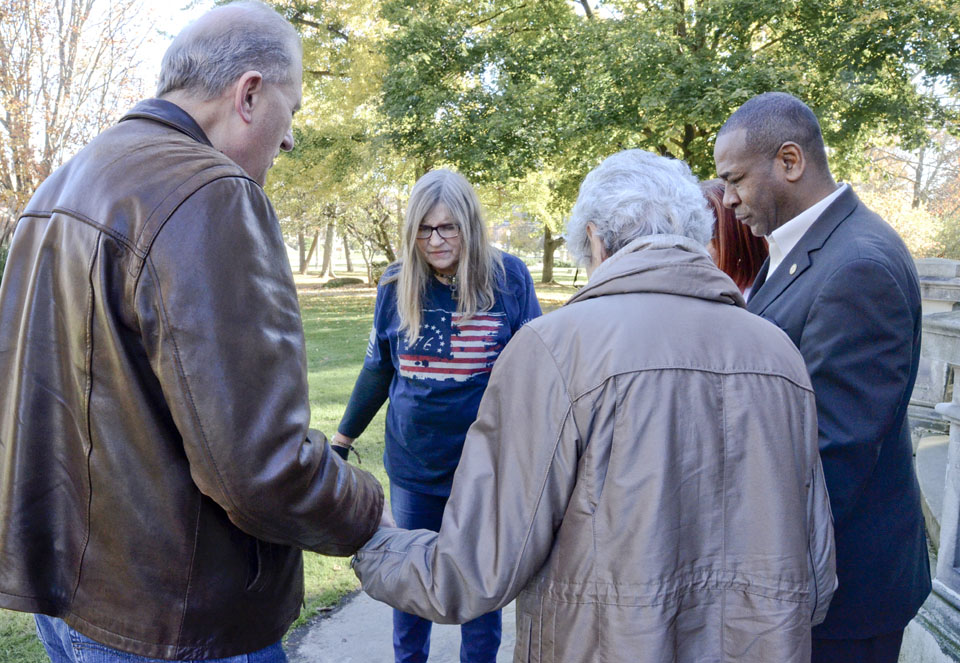 110716...R ELEX-PRAYER 1...Warren...11-07-16... Pastor Dan Barker, from Cortland Trinity Church, left, Andra (correct) Lance of Warren, 2nd from left, Bonnie Williams of Cortland, hidden behind Franklin, Warren Mayor Doug Franklin, far right, and Jo Lawrence of Warren, 2nd from right back to camera, pray together in front of City Hall for the upcoming election...by R. Michael Semple