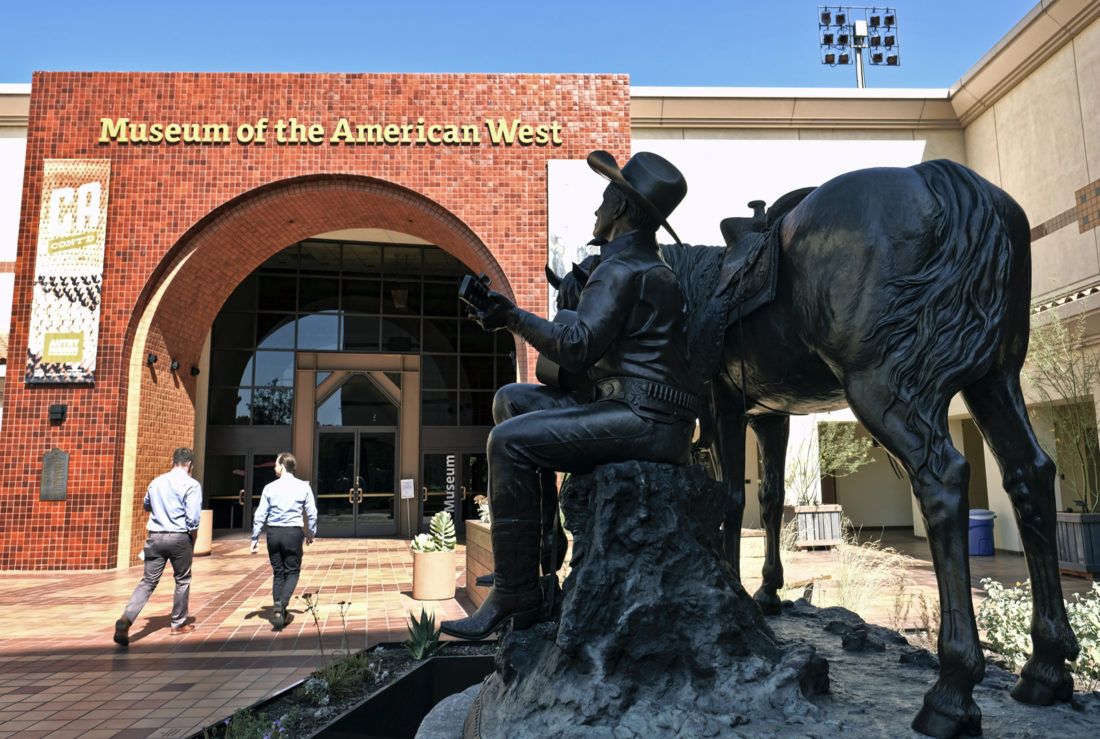 In this Tuesday, Oct. 4, 2016 photo, visitors walk by a statue of Gene Autry the entrance to the Autry Museum in Los Angeles. An expansion to the site, opening Sunday, Oct. 9, 2016, includes a garden of native Western flora, as well as new galleries showcasing hundreds of Native American works, some from present day, others centuries old, many never seen publicly. (AP Photo/Richard Vogel)