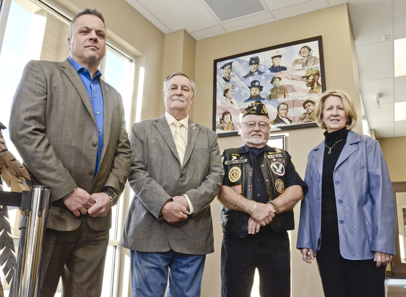 111016...R VETS PORTRAIT...Warren...11-10-16... From left: Herman Breuer, Director of Veteran Services for Trumbull County, veteran Gary Gutelius, veteran Ken David, and artist Marty Young...All standing in front of veterans portrait hanging in the lobby of the TC Veterans Resource Center in downtown Warren...by R. Michael Semple