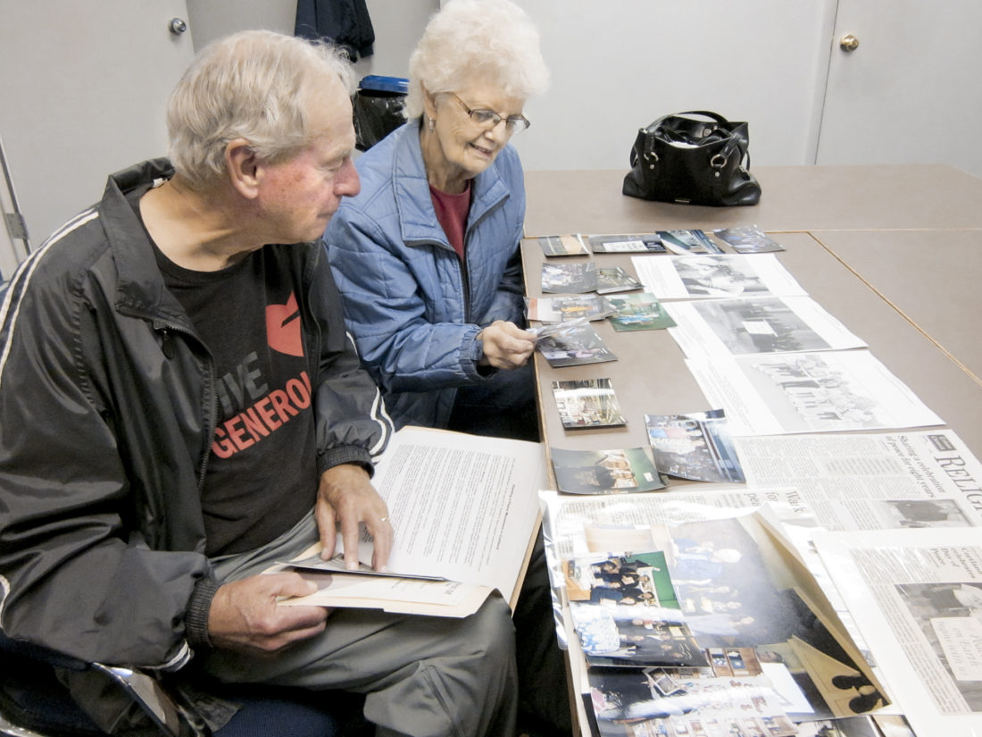 Tribune Chronicle / Burton Cole  Clyde, left, and Jean Bolinger leaf through photographs and news clips from their time as owners of The Book Nook in Warren and of the Trumbull County peace celebrations that Bolinger organized beginning in 2006.