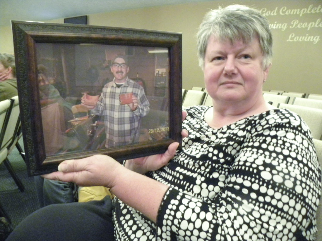 Tribune Chronicle/Andy Gray Brenda Lancaster of Warren holds up a photo of her younger brother, Charlie Robinson, who committed suicide in June. Lancaster attended the 18th Candlelight Vigil for National Suicide Survivors Awareness Day on Saturday at Victory Christian Center, Warren Campus.