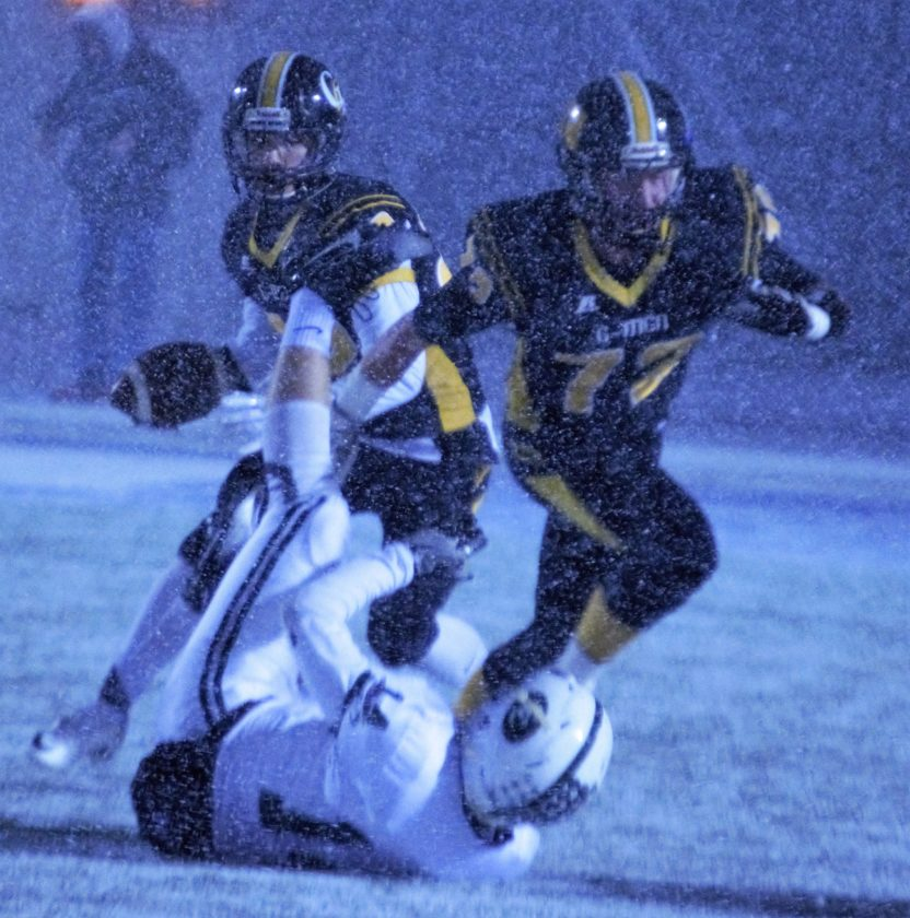Anthony DeNigris (with ball) of Garfield follows Cole Dean, who knocked Gunnar Eberhart of Canton Central Catholic to the ground during a snow storm in the Division V, Region 17 championship game at Uniontown Lake on Saturday night.