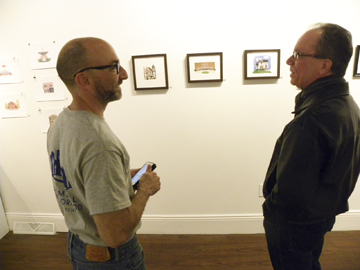 Tribune Chronicle/Andy Gray  Artist Alex Savakis, left, talks with Vince D'Onofrio of Newton Falls at the opening reception for Savakis' illustrations of Warren landmarks, which will be on display through December at Trumbull Art Gallery.