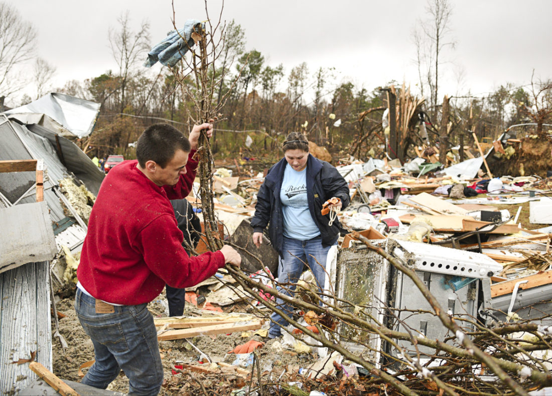 Chris Graves, left, and Jennifer Jeske sort through items Wednesday, Nov. 30, 2016, from the remains of a mobile home where two people were killed in Polk County after a tornado swept through the area early Wednesday. A suspected tornado was responsible for the death of a husband and wife in southern Tennessee's Polk County, while an unknown number of others were injured, said Tennessee Emergency Management Agency spokesman Dean Flener. (Angela Lewis/Chattanooga Times Free Press via AP)