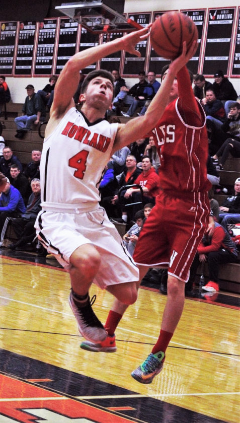 Tribune Chronicle / Bob Ettinger Nate Leventis of Howland takes the ball to the basket Tuesday night as Trent Johnson of Niles defends.