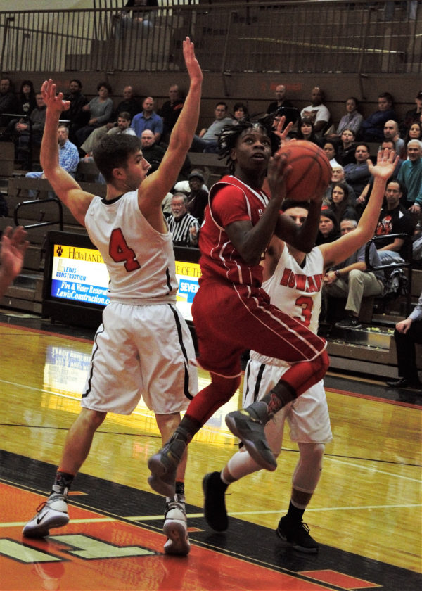 Tribune Chronicle / Bob Ettinger Da'Jon Motley of Niles spins as he gets off a shot against Nate Leventis of Howland.
