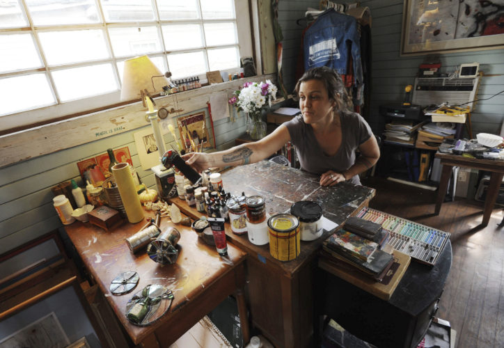 """In this Wednesday, March 29, 2017 photo, artist Catherine Edgerton works on stained-glass kaleidoscopes in her home studio for her upcoming exhibit """"Bottled Light"""" exploring mental health through books, drawings, and stained-glass kaleidoscopes, in Durham N.C. (Bernard Thomas /The Herald-Sun via AP)"""