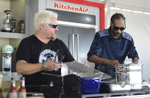 This Feb. 26, 2017 photo made available by WorldRedEye.com, shows rapper Snoop Dog, right, and Chef Guy Fieri, cooking together during a demonstration at the South Beach Wine & Food Festival in Miami Beach, Fla. Rappers Snoop, Action Bronson and Rev Run are ushering the culinary world into an era where shows like ÒÒMartha and SnoopÕs Potluck Dinner PartyÓ are a hit and rappers like 2 Chainz drop cookbooks along with their albums. (Ryan Troy/WorldRedEye.com via AP)