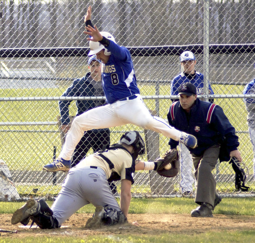 Jake Kocab of Grand Valley hurdles Windham catcher Blaze Angle to avoid the tag as umpire Steve Perry watches the play in Northeastern Athletic Conference action on Thursday night at Grand Valley. Kocab was out on the play.