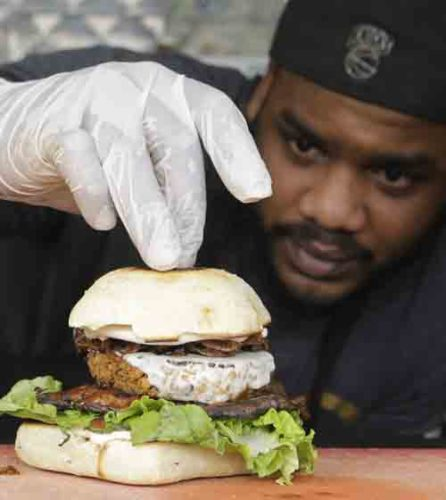 In this March 1, 2017, photo, chef Miguel Navarro inspects a Le Bleu hamburger, made with caramelized onions and blue cheese on top of portobello mushroom and lettuce, at the Atlas Meat-Free Delicatessen in Miami. When Ryan Bauhaus first started experimenting with faux meats, he fixated on recreating that subtle blood taste, settling on a tomato paste blend to mimic the acidic, iron flavor. The fatty part of meat was also not to be forgotten. Bauhaus boiled down mushrooms until he got the desired gelatinous, rubbery fat found on the back of a roast. (AP Photo/Alan Diaz)