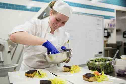 Special to the Tribune Chronicle Janice Campbell, a 2014 Bristol High School graduate and a culinary student at Cuyahoga Community College, prepares three-course dinners for the Ultimate Culinary Clash in Cleveland. She will compete for the national title in May in San Francisco.