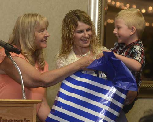 "Michael Bingham, 4, right, is eager to see what is in the gift bag presented to his paternal grandmother Cynthia Bingham, left,  while being held by his paternal aunt Courtney Bingham, center, during the Trumbull County Children Services ""Rising Up and Moving On"" Community luncheon...by R. Michael Semple"