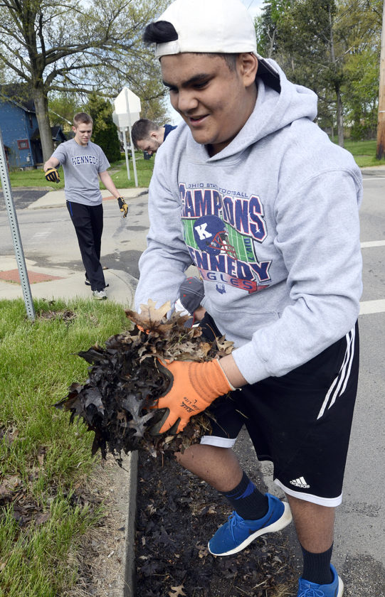 Tribune Chronicle / R. Michael Semple  Warren John F. Kennedy High School student Dylan Massacci, 16, cleans debris from the corner of Milton Street and Willard Avenue SE Friday morning during JFK's service retreat day.