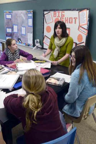 Tribune Chronicle / R. Michael Semple A+ Teacher Kathleen Bronson, center, discusses literature with eight-grade students Ally Potts, left; Alexa Motichko, right; and Dezaray Dietrich, back to the camera, at Champion Middle School. Branson is one of 20 educators who were selected for the 27th annual A+ Teacher awards, which honor outstanding teachers in Trumbull County.