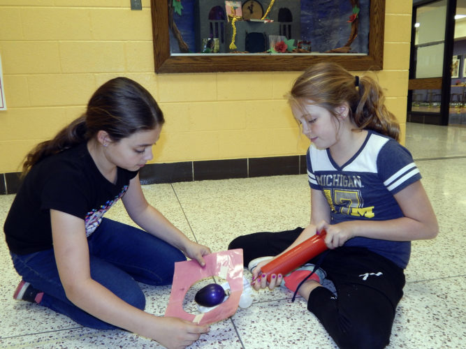 Tribune Chronicle photos / Bob Coupland Lordstown Elementary School fifth graders Carly DeBernardo, and Megan Mistovich, both 10, work on their jet toy in the hallway as part of the ''World in Motion'' program with General Motors.