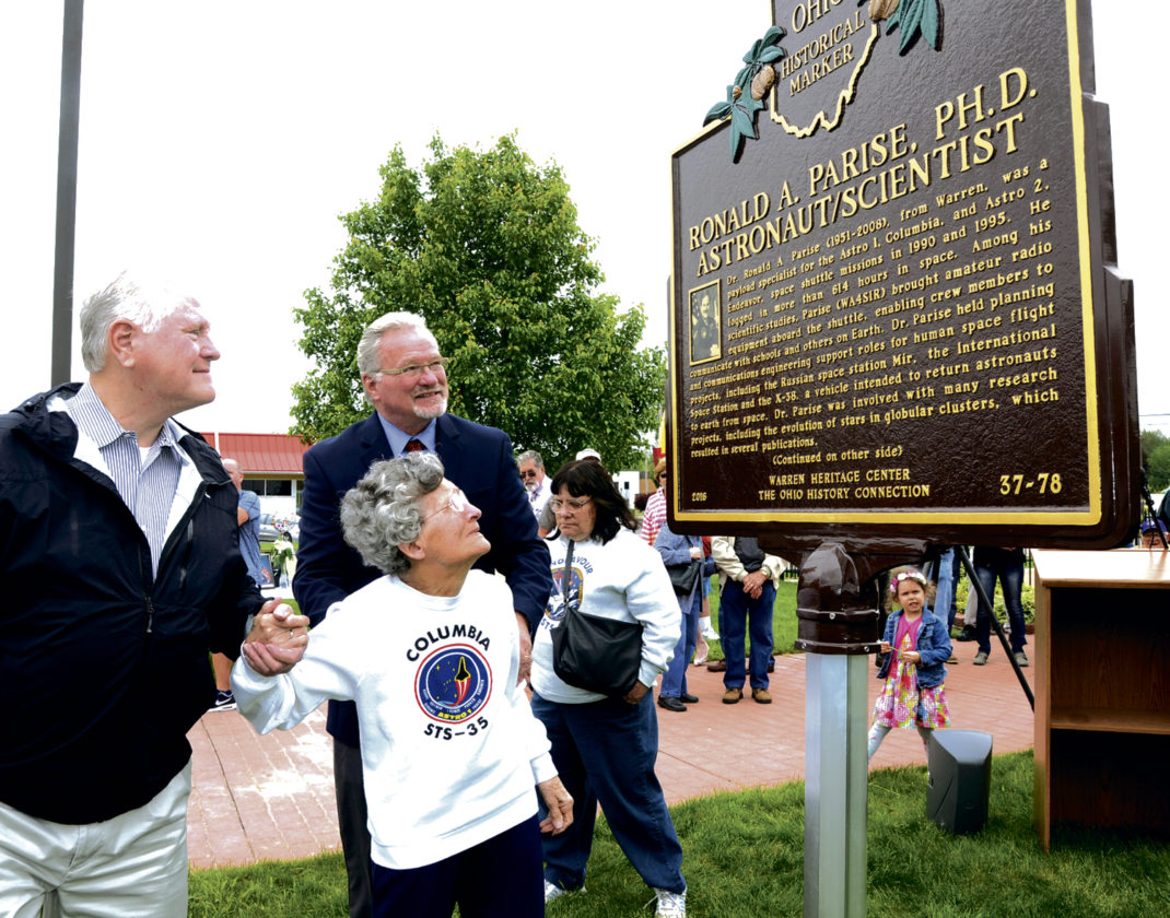 Tribune Chronicle / R. Michael Semple  Cathryn Parise, center, mother of astronaut and Warren native Ronald A. Parise, views the Ohio Historical Marker dedicated to her son that was unveiled Wednesday at the site of the Neil Armstrong First Flight Lunar Module in Warren. Ronald Parise would have been 66 on Wednesday. He died in 2008 at the age of 56. With Cathryn is Fred Pisanelli, left, a childhood friend of Ronald Parise, and James Valesky, founder of the Warren Heritage Center, which raised money for the marker.